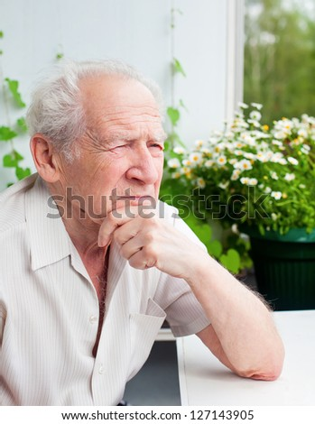 portrait of a pensive senior man holding his hand near his face, he is thinking about something - stock photo
