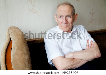 portrait of a pensive senior man with crossed arms, he is looking somewhere - stock photo