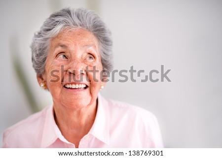 Portrait of a pensive senior woman smiling - stock photo