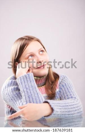 Portrait of a pensive teen girl, studio shot - stock photo