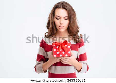Portrait of a pensive woman holding gift box isolated on a white background