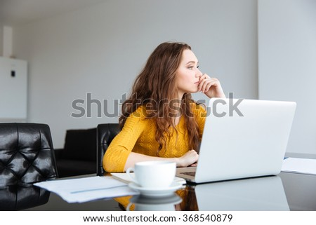 Portrait of a pensive woman sitting at the table with laptop computer at home - stock photo