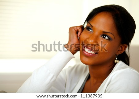 Portrait of a pensive young black woman looking up at home indoor. With copyspace