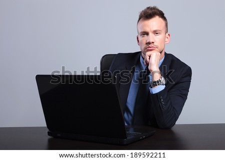 portrait of a pensive young business man sitting in front of his laptop and looking into the camera while holding his hand on his chin. on a gray studio background
