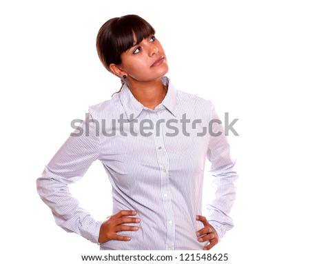 Portrait of a pensive young business woman looking up standing over white background - copyspace - stock photo