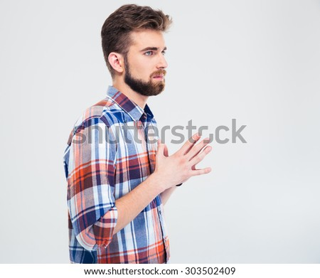 Portrait of a pensive young man standing isolated on a white background. Looking away - stock photo