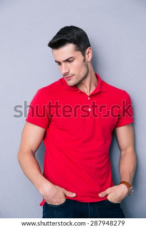 Portrait of a pensive young man standing over gray background - stock photo