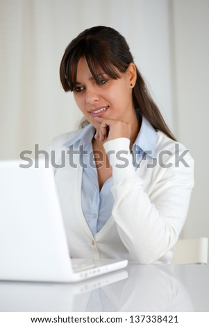 Portrait of a pensive young woman reading on laptop screen at soft colors composition