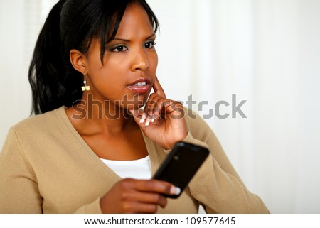 Portrait of a pensive young woman using her cellphone at soft colors composition - stock photo