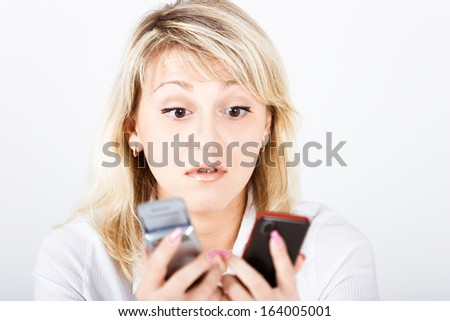 Portrait of a perplexed girl with two mobile phones - stock photo