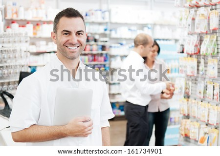 Portrait of a pharmacist holding a tablet. In the background we can see two customers at the pharmacy - stock photo