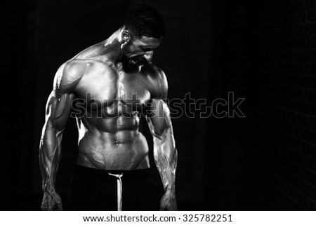 Portrait Of A Physically Fit Man Showing His Well Trained Body And Holding Chains - stock photo