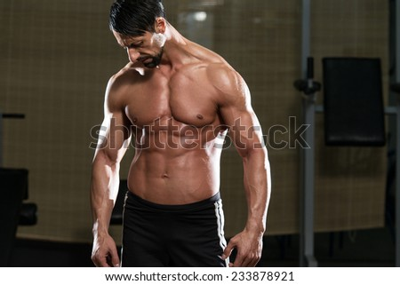 Portrait Of A Physically Fit Young Man - Flexing Muscles - stock photo