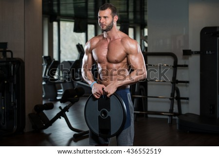 Portrait Of A Physically Young Man Holding Weights In Hand
