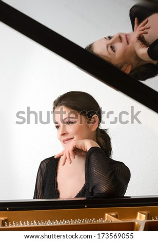Portrait of a pianist by the grand piano with reflection - stock photo