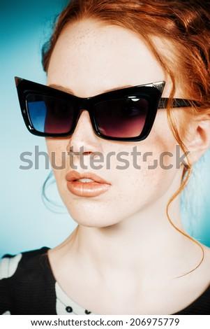 Portrait of a pin-up girl wearing stylized sunglasses. Fashion. Retro style. - stock photo
