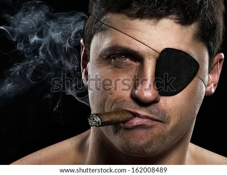 Portrait of a pirate with a cigar looking camera - stock photo