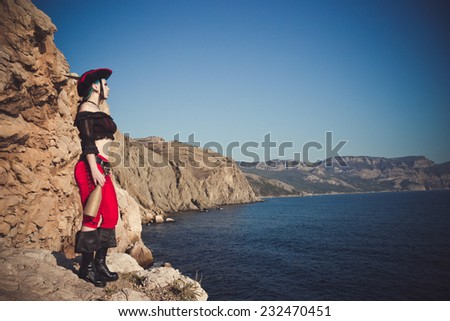 Portrait of a pirate woman at the beach. In anticipation of a pirate ship
