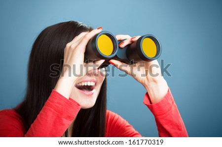Portrait of a playful girl looking through the binoculars, studio shot on blue background - stock photo