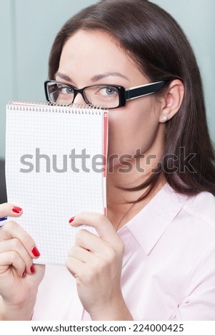 Portrait of a playful woman hiding behind the notebook - stock photo