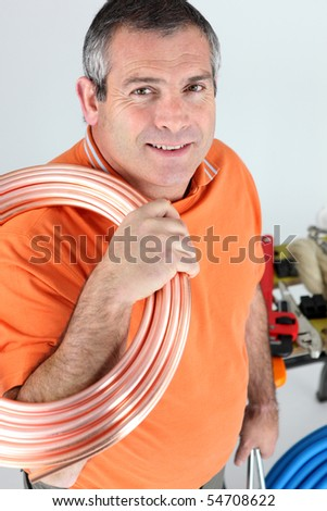 Portrait of a plumber with a copper tube - stock photo