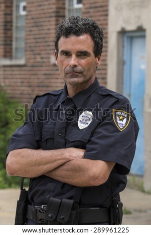 Portrait of a police officer, arms crossed, serious face - stock photo