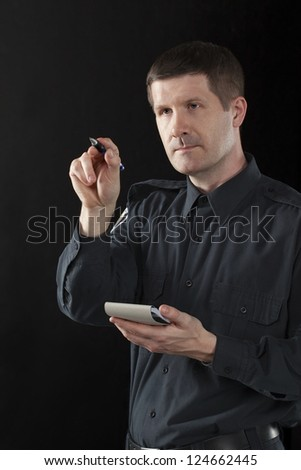 Portrait of a police officer pointing someone over black background - stock photo