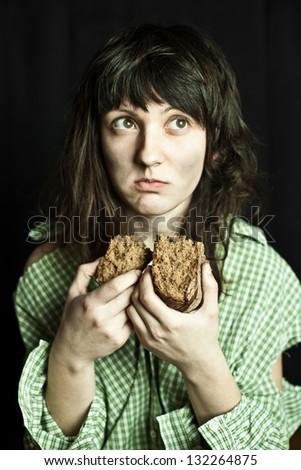 portrait of a poor beggar woman eating bread - stock photo
