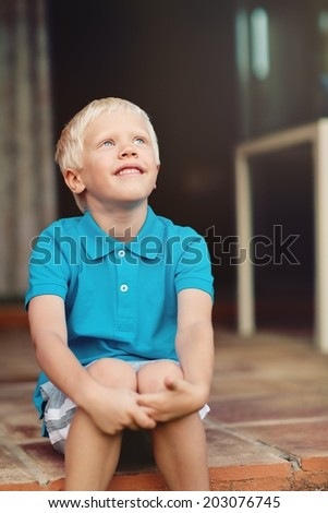 Portrait of a positive blond boy in a blue shirt  outdoor.  - stock photo