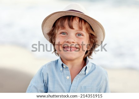 Portrait of a positive boy (4-5 years) in a hat on the beach on a summer day .Outdoor, close up. - stock photo