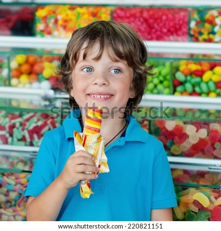 Portrait of a positive boy (4-5 years) with ice cream . Background of sweets .Outdoor, close up.  - stock photo