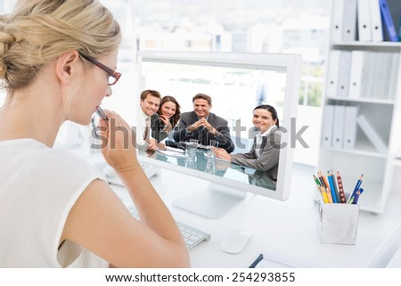 Portrait of a positive manager with his team against rear view of a female photo editor working on computer - stock photo