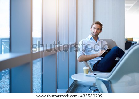 Portrait of a positive young businessman sitting in a modern corporate environment, looking at the camera while holding his diary, with gentle sunflare through the windows - stock photo