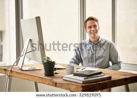 Portrait of a positive young businessman smiling confidently while sitting behind his desk in a light and bright office space - stock photo