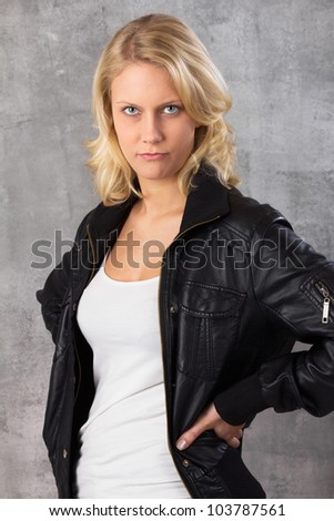 Portrait of a pouting young blonde woman, with hands on hips looking at the camera. Studio shot against a gray background. - stock photo