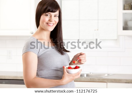 Portrait of a pregnant happy woman eating a healthy meal in kitchen at home - stock photo