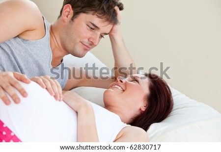 Portrait of a pregnant woman and of her husband lying on the bed at home
