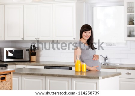 Portrait of a pregnant woman at home drinking orange juice - stock photo