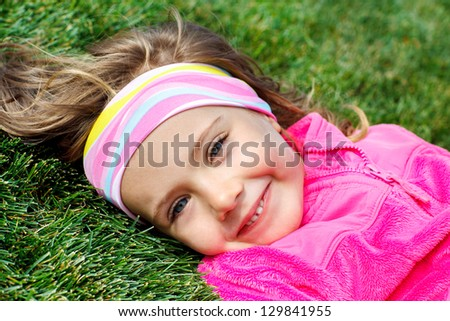 Portrait of a preschool girl on green grass - stock photo