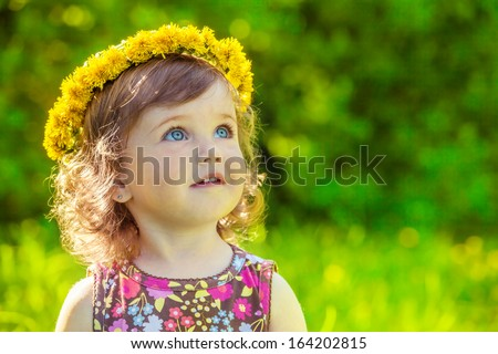 Portrait of a preschool girl with yellow flowers head wreath on - stock photo