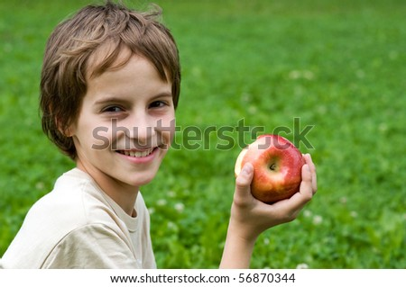 Portrait of a preteen boy with a apple in his hand and green grass in the background - stock photo