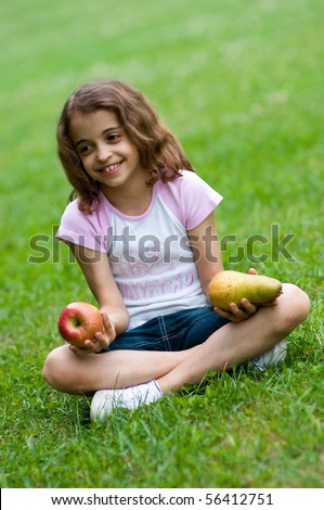 Portrait of a preteen girl with an apple and a plum in her hands and green grass in the background - stock photo