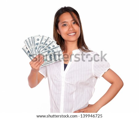 Portrait of a pretty asiatic young woman with cash dollars looking at you against white background