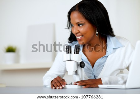 Portrait of a pretty black female working with a microscope at laboratory - stock photo