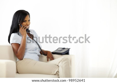 Portrait of a pretty black young woman talking on phone while resting at home - stock photo