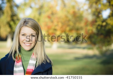 Portrait of a Pretty Blond Teen Girl Standing in a Park - stock photo