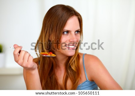 Portrait of a pretty blonde woman eating healthy meal at home indoor - stock photo