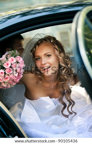 Portrait of a pretty bride in a car - stock photo