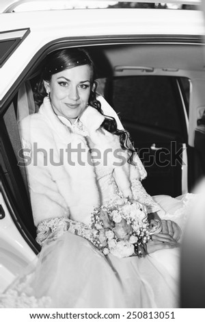 Portrait of a pretty bride in a car. close-up portrait of a pretty shy bride in a car window - stock photo