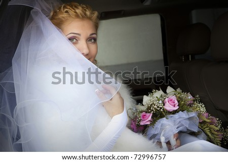 Portrait of a pretty bride in a car window - stock photo